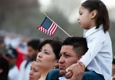 daughter on fathers shoulders holding an American flag